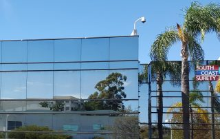 Glass building with South Coast Surety sign and palm trees